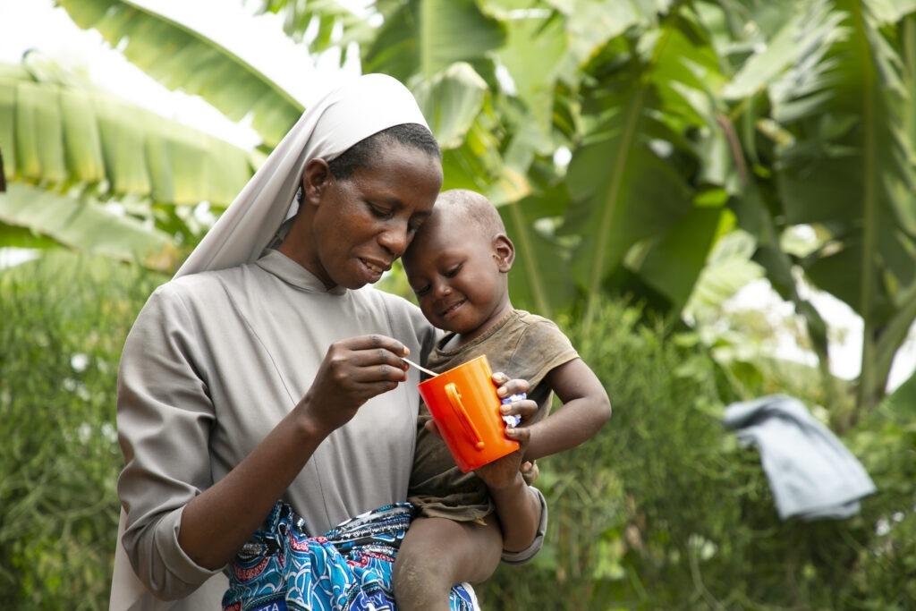 Sœur Cécilia nourrissant un petit enfant, Rwanda